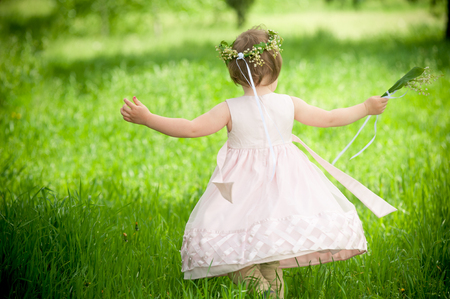 unruly: Happy baby girl outdoors with a bouquet of lilies, childhood Stock Photo