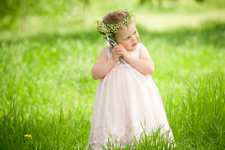 children love: sweet baby girl outdoors with a bouquet of lilies, childhood
