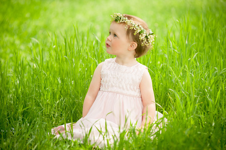 merrymaking: Sweet baby girl in wreath of flowers sitting on green grass outdoors