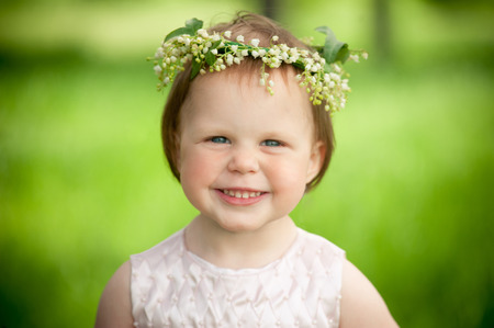 mirth: Sweet baby girl in wreath of flowers smiling outdoors Stock Photo