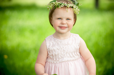 chuckle: Sweet baby girl in wreath of flowers smiling outdoors Stock Photo