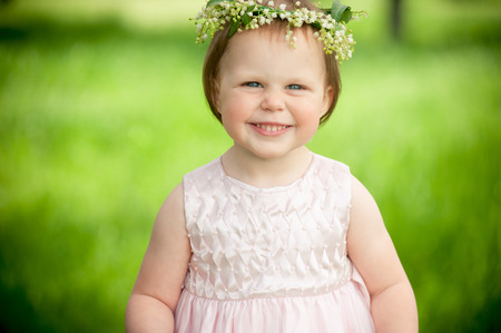 merrymaking: Sweet baby girl in wreath of flowers smiling outdoors Stock Photo