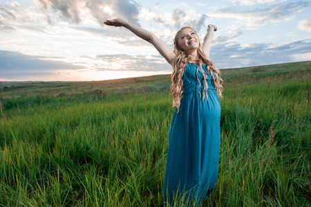 woman hands up: Happy pregnant woman stand on meadow