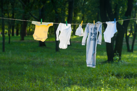 hangs: Baby Clothes dry on a rope outdoors