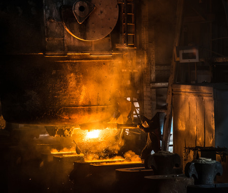 ferrous foundry: Steelworker pours liquid metal into molds from tank