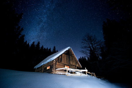 Beautiful wooden house in the winter forest under the stars Фото со стока