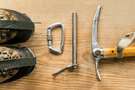 crampon: climbing equipment: trekking shoes, ice tools, ice ax, ice screws, crampons, carbine on wooden background, top view