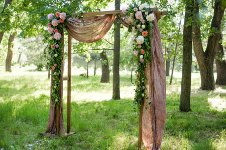 Beautifully decorated with flowers arch for a wedding ceremony. Wedding decor.