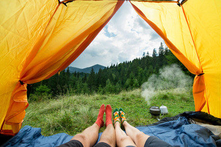 legs of a couples of man and woman in a tent outdoors Фото со стока