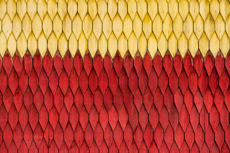 Old weathered wooden wall with ornament painted in red and yellow. Vintage texture Background.