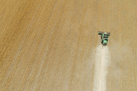Modern combine harvester working on the wheat crop. Aerial view. Stock Photo