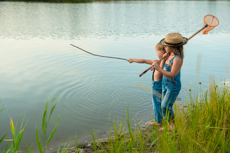 Two children with a butterfly net near the river Stock Photo