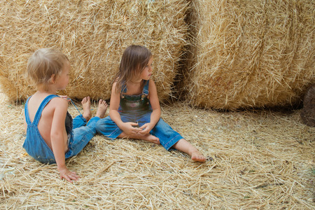 Two children sits on a haystack Stock Photo