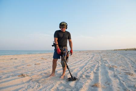 hombre con un detector de metales en una playa de arena de mar Foto de archivo