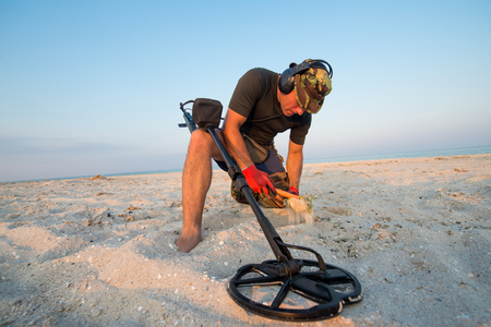 Man with a metal detector on a sea sandy beach