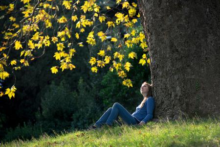 Girl sitting on the grass under a maple tree in autumn 写真素材