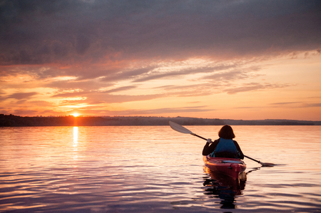 Woman in a kayak on the river on the scenic sunset 写真素材