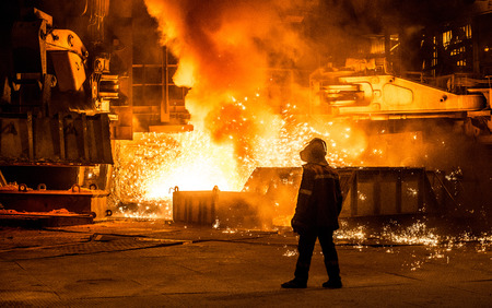 Steelworker vicino a un altoforno con scintille