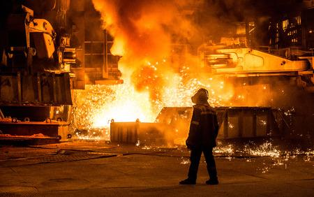Trabajador siderúrgico cerca de un alto horno con chispas