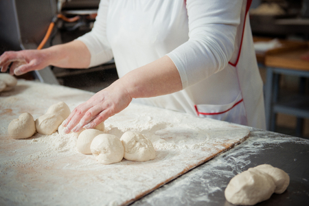Woman baker make buns from dough