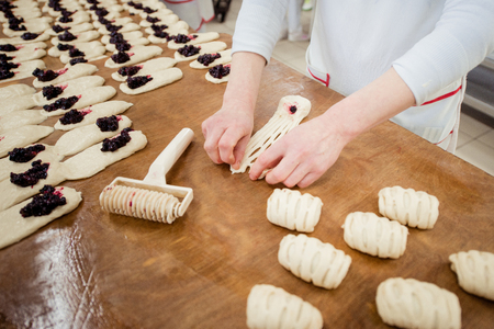 Woman baker make buns with fruit filling from dough Stockfoto