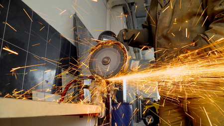 Closeup of worker using a grinder cuts metal in a workshop