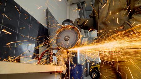 Il primo piano del lavoratore che utilizza una smerigliatrice taglia il metallo in un'officina