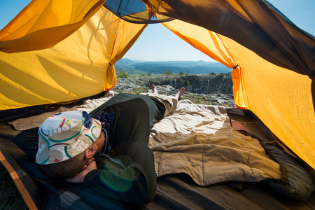 Traveler is resting inside a tent outdoors