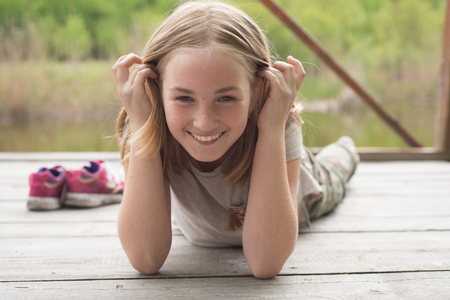 Adorable smiling teen girl lying on her stomach on a wooden bridge