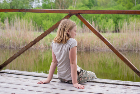 Teen girl sitting on a wooden bridge near the river