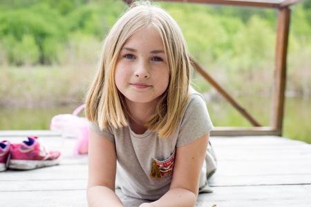 Adorable adolescente souriante allongée sur le ventre sur un pont en bois Banque d'images