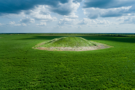 Scenic view of the burial mound of the Scythian king in a green field. Aerial view. Фото со стока