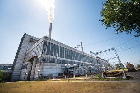 Thermal Power Plant Building with a smoking pipe Фото со стока
