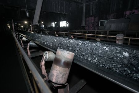 Black coal on a conveyor belt. The production process in the Thermal Power Plant.
