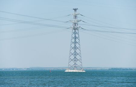 High-voltage pylon of power lines on the river