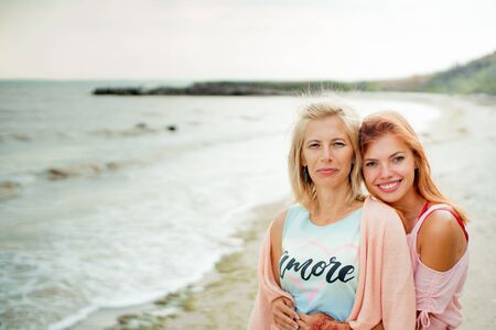 Adult daughter hugs mom on the sea shore and both are smiling