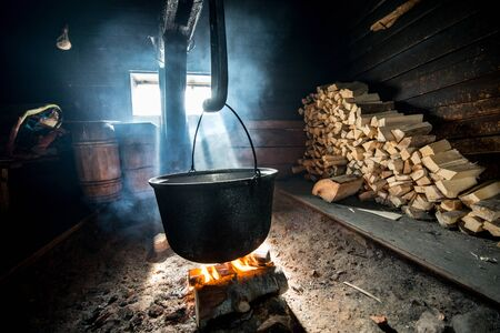Cauldron on bonfire in a wooden house, cooking cheese