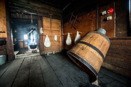 Herstellung von frischem hausgemachtem Hüttenkäse in Käsetuch in einem Holzhaus