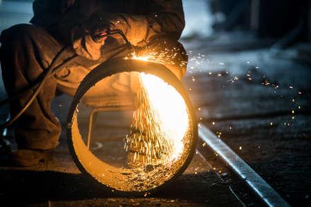 Worker doing a industrial welding in a workshop Фото со стока