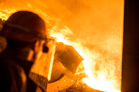 Steelworker when pouring liquid metal from tanks in the molds