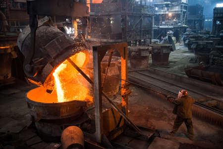 Steelworker at work near the tanks with hot metal