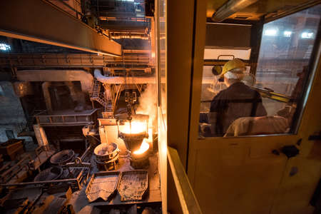 Worker operates in the cabin of a cargo crane at the steel mill