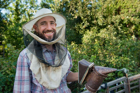 beekeeper in a protective mask smiling