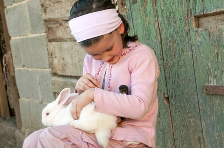 Little girl play with her rabbit