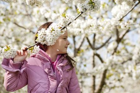 Swett little girl in a blossom cherry garden photo
