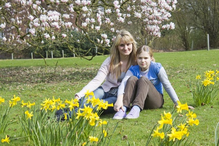 young woman and little girl in the park on a warm spring day photo