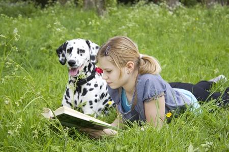 dog days: Una ni�a lee un libro al aire libre el d�a, c�lido de la primavera Foto de archivo