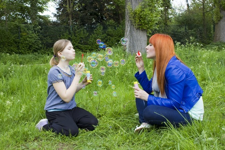 Little girl and young woman blowing soap bubbles photo