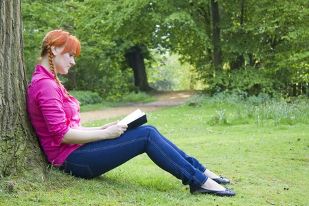Young beautiful girl with red hair reading a book photo