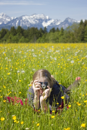 young girl taking photos by digital camera in the mountains photo